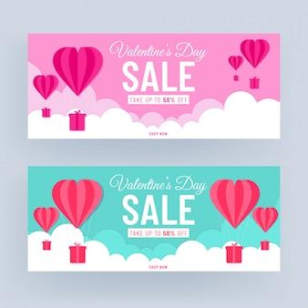 Diseño de encabezado o pancarta rosa y turquesa con oferta de descuento del 50% y globos de aire caliente en forma de corazón cortados en papel sobre fondo nublado para la venta del día de san valentín.
