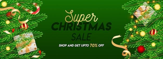 Diseño de encabezado o pancarta de súper venta de navidad con una oferta de descuento del 70%, hojas de pino, adornos, cajas de regalo y guirnaldas de iluminación decoradas sobre fondo verde.