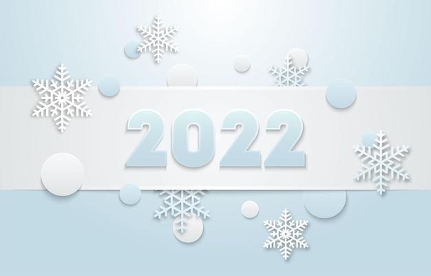El diseño vectorial de año nuevo 2022 con copos de nieve sobre un fondo azul.
