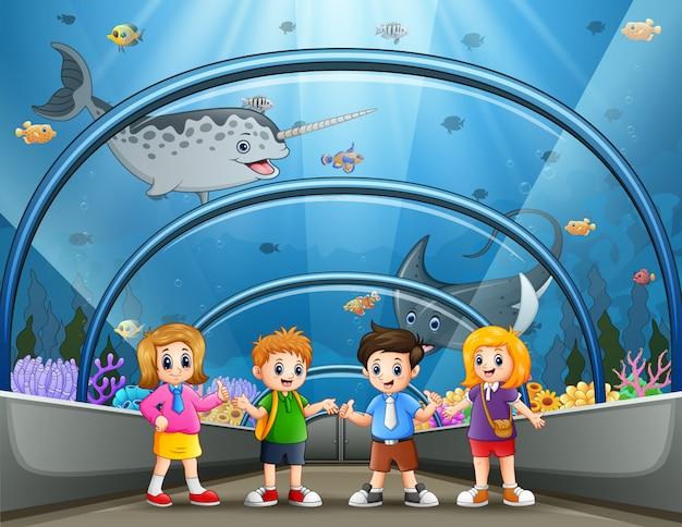 Divertidos escolares mirando peces en el acuario