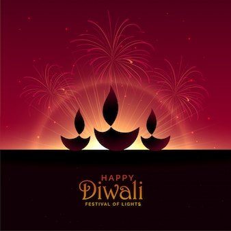 Diya de tres diwali con fuegos artificiales.