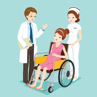 Doctor hablando con embarazada en silla de ruedas y enfermera