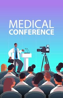 Doctor masculino afroamericano dando discurso en la tribuna con micrófono conferencia médica medicina concepto de salud sala de conferencias interior vertical ilustración vectorial