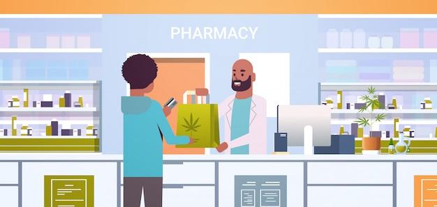 Doctor masculino farmacéutico dando paquete de cannabis medicinal al cliente afroamericano en el mostrador de la farmacia moderna farmacia interior medicina concepto de salud retrato horizontal