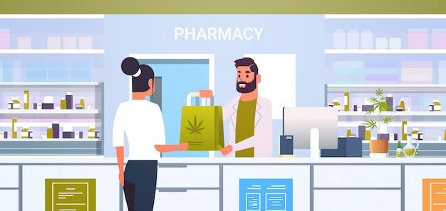 Doctor masculino farmacéutico dando paquete de cannabis medicinal al cliente femenino en el mostrador de la farmacia moderna farmacia interior medicina concepto de salud horizontal retrato