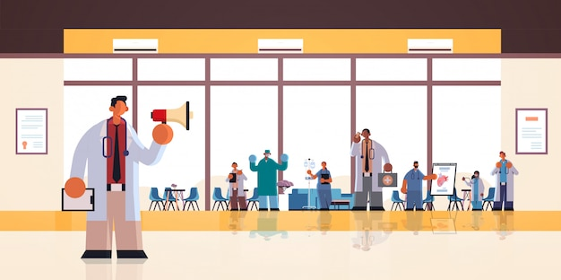 Doctor de sexo masculino que usa el altavoz que hace el anuncio para los trabajadores del hospital de raza mixta en medicina uniforme concepto de salud clínica moderna oficina interior plano horizontal de longitud completa