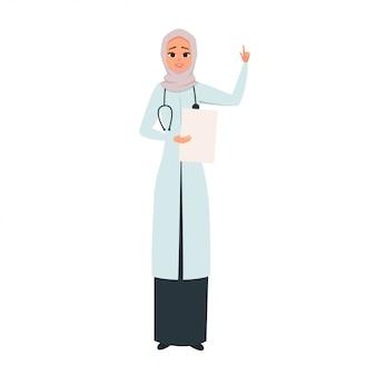 Doctor sonriente en hijab con la mano en alto como señal de atención.