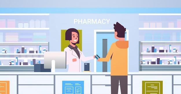 Doctora farmacéutico tomando tarjeta de crédito del paciente masculino paciente en el mostrador de la farmacia moderna farmacia interior medicina concepto de salud horizontal retrato
