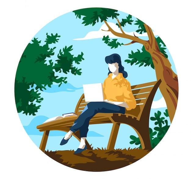Una donna giovane seduta sulla panchina al parco che lavora al computer portatile