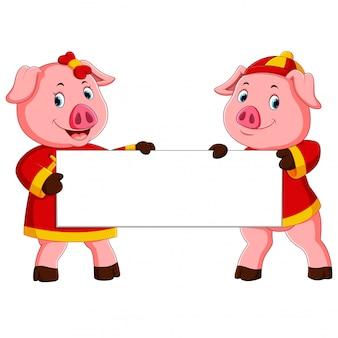 Dos cerdos lindos sostienen la pizarra blanca para el año nuevo chino