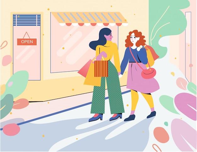 Dos chicas salen de la tienda con bolsas de compras.