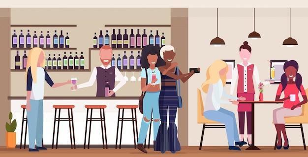 Dos chicas tomando una foto autofoto en la cámara del teléfono inteligente mezclar raza personas relajándose en el bar bebiendo cócteles barman y camarera sirviendo a los clientes moderno café interior horizontal longitud completa