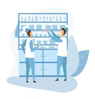 Dos cocineros masculinos de pie cerca de armario con utensilio