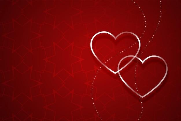 Dos corazones plateados sobre fondo rojo del día de san valentín