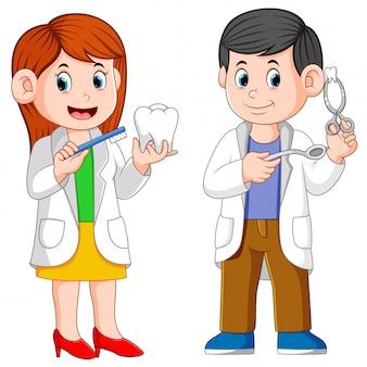 Los dos dentistas están sosteniendo las herramientas para la práctica.