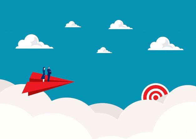 Dos empresarios de pie en avión de papel rojo volando en el cielo