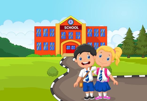 Dos estudiantes felices de pie frente al edificio de la escuela