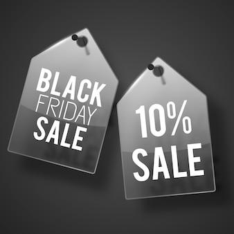 Dos etiquetas de venta de color gris oscuro clavadas en la pared con descripción de venta de viernes negro