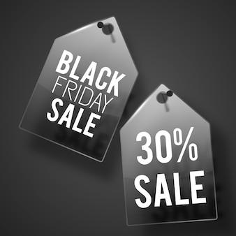 Dos etiquetas de venta de viernes negro en la pared con sombras y textos en blanco