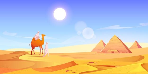 Dos hombres y camellos en el desierto egipcio con pirámides