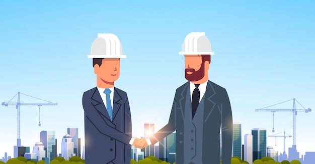 Dos hombres de negocios apretón de manos sobre el sitio de construcción de la ciudad