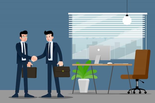 Dos hombres de negocios de pie y se dan la mano en la oficina.