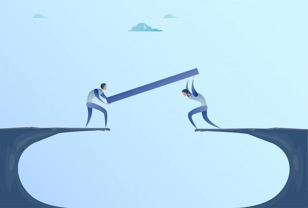 Dos hombres de negocios que construyen un puente sobre el concepto de trabajo en equipo de la cooperación de cliff gap mountain