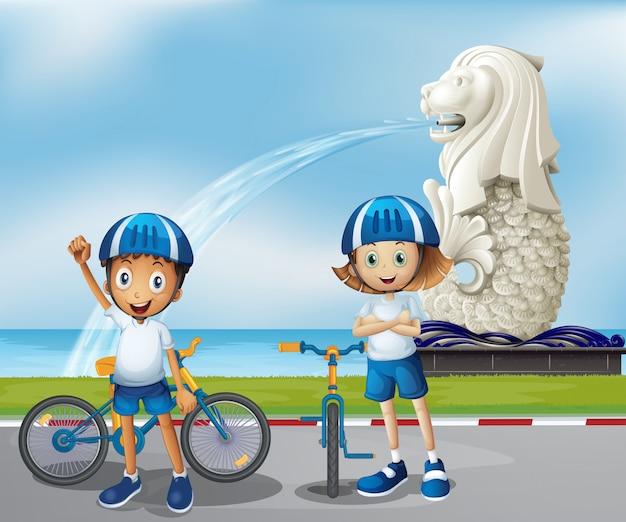 Dos lindos ciclistas de pie en la parte delantera del merlion