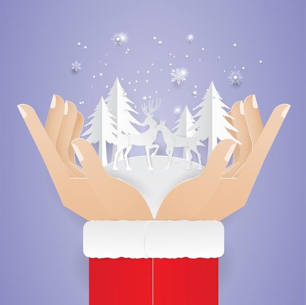 Dos manos humanas sosteniendo renos y un vale de árbol de navidad