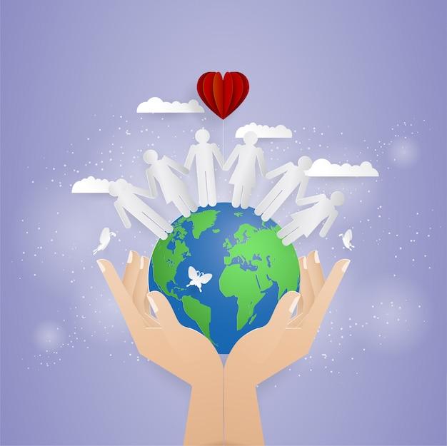 Dos manos sosteniendo el mundo y las personas en el mundo.