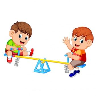 Dos niño jugando en balancín