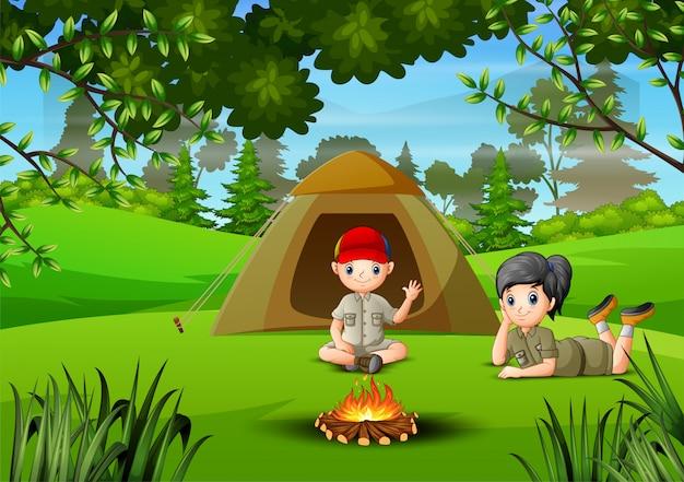 Dos niños acampando en el bosque