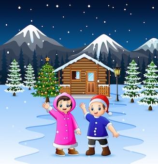 Dos niños agitando la mano frente a la casa de madera nevada