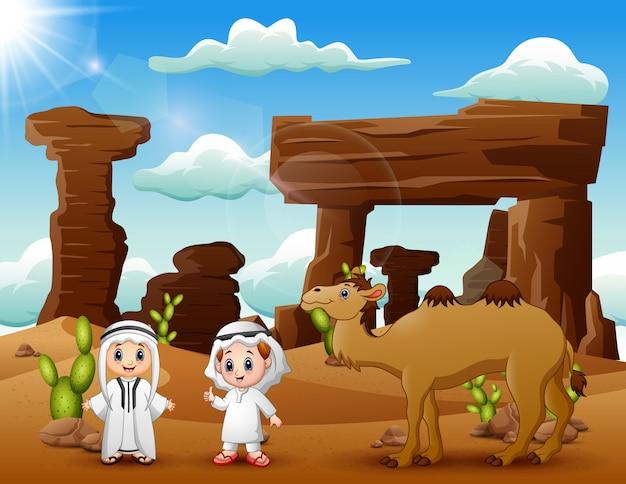 Dos niños árabes con camellos en el desierto.