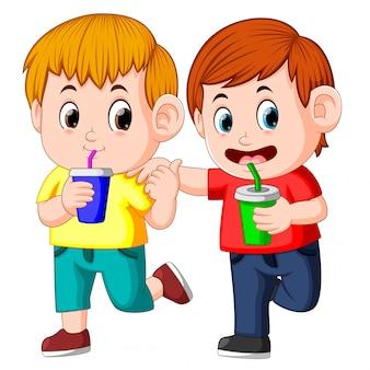 Dos niños bebiendo refrescos en una taza de papel
