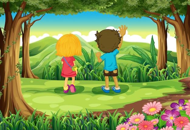 Dos niños en el bosque mirando las montañas.