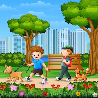 Dos niños caminando con su perro en el parque de la ciudad.