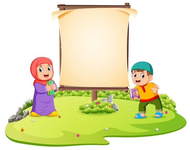 Dos niños están de pie en el jardín verde cerca del marco en blanco.