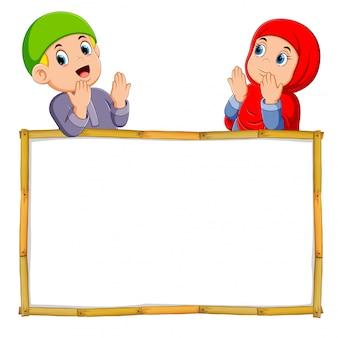 Los dos niños están rezando sobre el marco de madera en blanco.