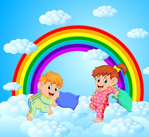 Dos niños felices están luchando una almohada con un paisaje de arco iris