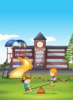 Dos niños jugando balancín en la escuela