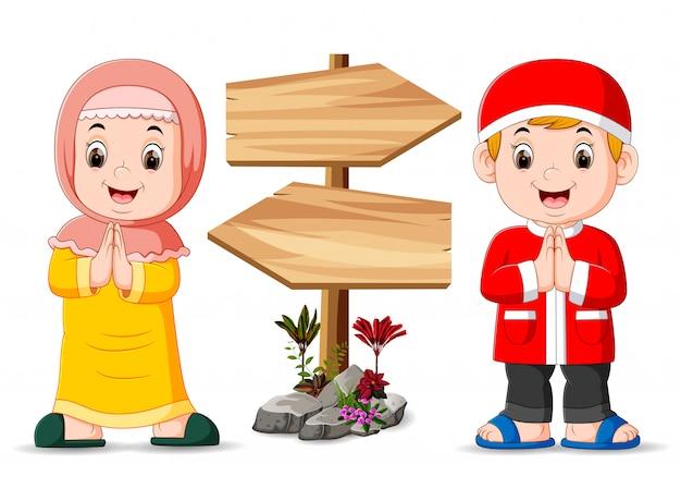 Los dos niños musulmanes están parados cerca del poste indicador de madera.