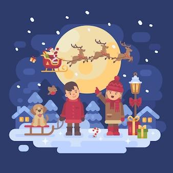 Dos niños con perro jugando afuera en una noche de invierno