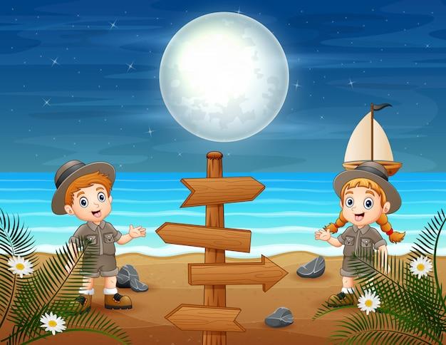 Dos niños de safari en la playa de noche