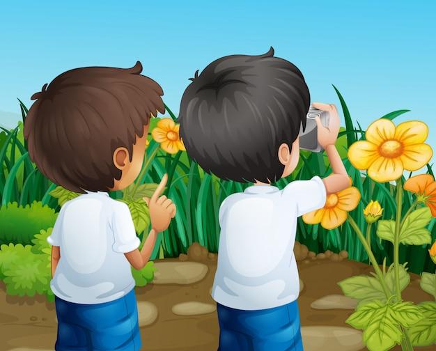 Dos niños tomando fotos de las flores.