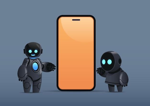 Dos robots de pie cerca del teléfono inteligente con tecnología de inteligencia artificial de carácter robótico de pantalla en blanco