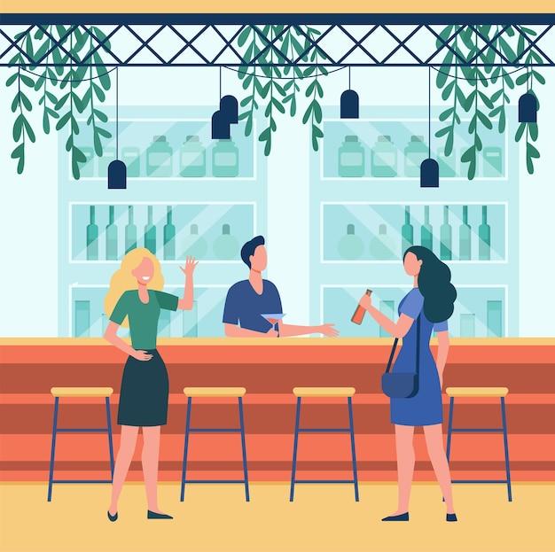 Dos señoras bebiendo en el bar y hablando con el barman