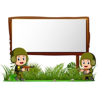 Dos soldados por letrero de madera en la jungla