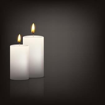 Dos velas blancas realistas en la oscuridad con reflejo.