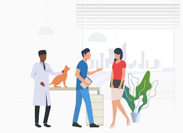 Dueño del gato visitando y hablando con médicos veterinarios